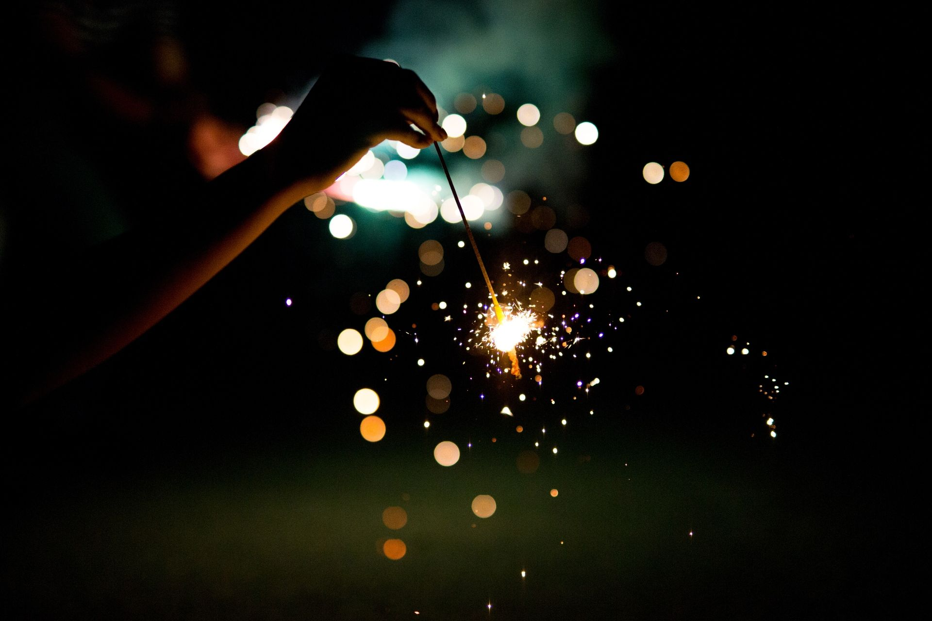 Person off screen holding a sparkler that's burning