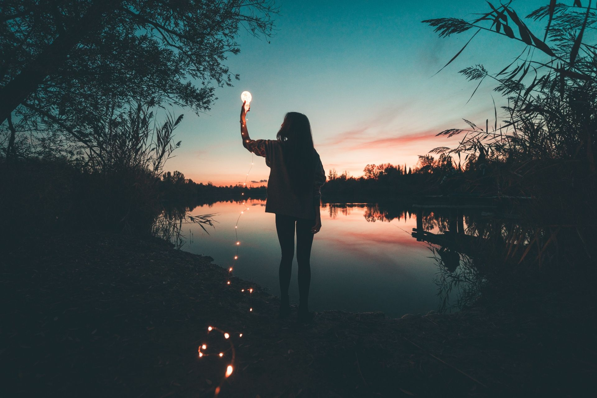 Woman standing on the water's edge of a lake, surrounded by greenery, holding a string of lights up to meet the moon. It gives the effect that she's captured the moon.