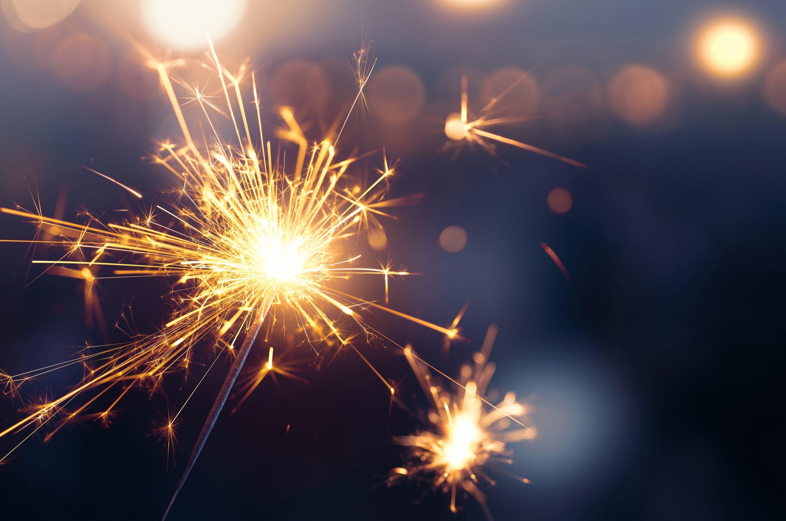 Sparkler burning in the bottom left side of photo